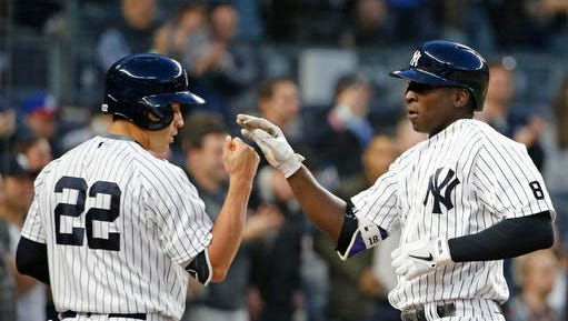 New York Yankees' Jacoby Ellsbury (22) greets Didi Gregorius at the plate after Gregorious hit a second-inning solo home run in a baseball game against the Oakland Athletics, Wednesday, April 20, 2016, in New York.