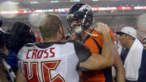 Denver Broncos quarterback Paxton Lynch (12) and Tampa Bay Buccaneers running back Alan Cross (45) shake hands after the Broncos defeated the Buccaneers 27-7 during an NFL football game Sunday, Oct. 2, 2016, in Tampa, Fla. They were college teammates at Memphis.