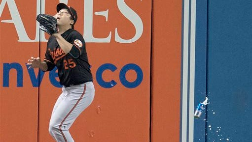 Baltimore Orioles' Hyun Soo Kim gets under a fly ball as a can falls past him during the seventh inning of an American League wild-card baseball game against the Toronto Blue Jays. A man was identified and charged was mischief in the incident.