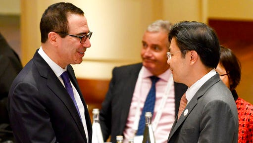 U.S. Treasury Secretary Steven Mnuchin, left, shakes hands with Lawrence Wong, Singaporean minister for national development, at the G20 finance ministers meeting in Baden-Baden, southern Germany, Friday, March 17, 2017.