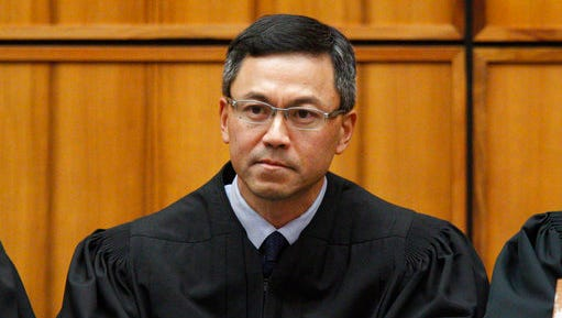 FILE  - This Dec. 2015 file photo shows U.S. District Judge Derrick Watson in Honolulu. Watson is hearing arguments Wednesday, March 29, 2017, in Honolulu, on whether to extend his temporary order blocking President Donald Trump's revised travel ban. But even if Watson doesn't put the ban on hold until the state's lawsuit is resolved, his temporary block would remain until he rules otherwise.