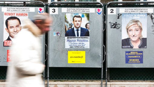 A man walks past electoral posters displaying the presidential candidates, Benoit Hamon, left, Emmanuel Macron, center, and Marine Le Pen in Paris, France, Monday, April 17, 2017. French centrist candidate Emmanuel Macron and far-right leader Marine Le Pen are hoping to bring in big crowds at competing rallies in Paris as the unpredictable race nears its finish.