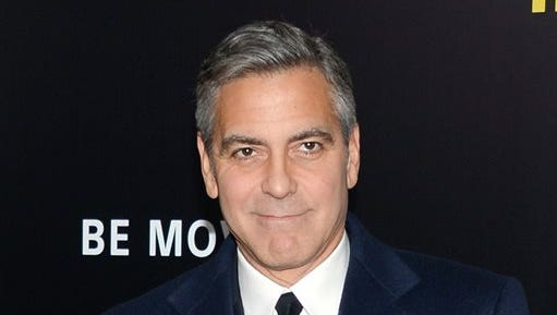 """Director and actor George Clooney attends the premiere of """"The Monuments Men"""" at the Ziegfeld Theatre in New York. Clooney, who married human rights lawyer Amal Alamuddin on Sept. 27 in Venice, Italy, made an appearance at New York Comic Con, Thursday for a panel on his upcoming film, """"Tomorrowland."""""""