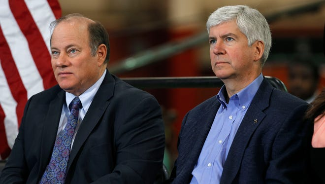 Detroit Mayor Mike Duggan, left, and Gov. Rick Snyder listen to a speaker at the IDEAL Group Thursday, Jan. 23, 2014 in Detroit.