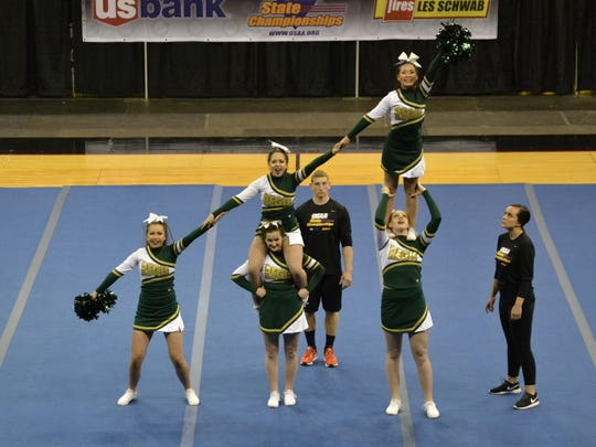 Regis cheerleaders, from left, Terri Chrestenson, Emily Adams (bottom), Claire Peters (top), Cheyenne Cox (bottom) and  Hannah Cui (top) build up their skills at the OSAA Cheer Championships.