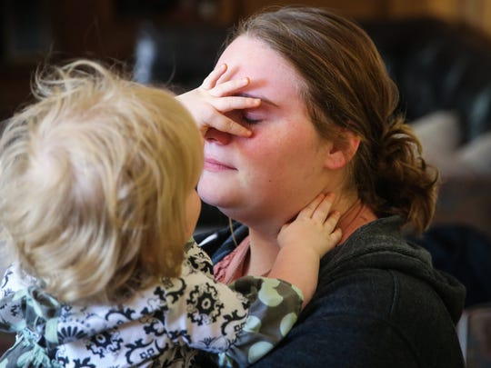 Ava Mykal, 1, wipes away tears from her mother's face Tuesday, April 24, 2018. Emerlene Crelia cried as she talked about her husband, Gaiden, who died in a crash last Friday.