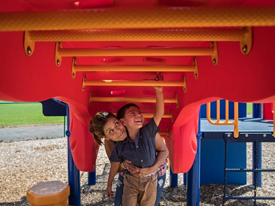 Vivian and Mathías play on monkey bars in the park during some down time. Vivian works odd jobs and cleans homes for money. The only assistance she has recieved in the past three years has been through her church.  July 13, 2018