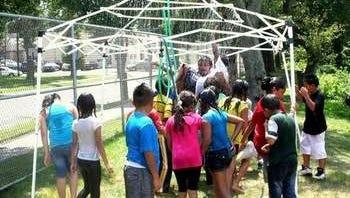 Children in New Brunswick's PLAY S.A.F.E. program cool off under a sprinkler.