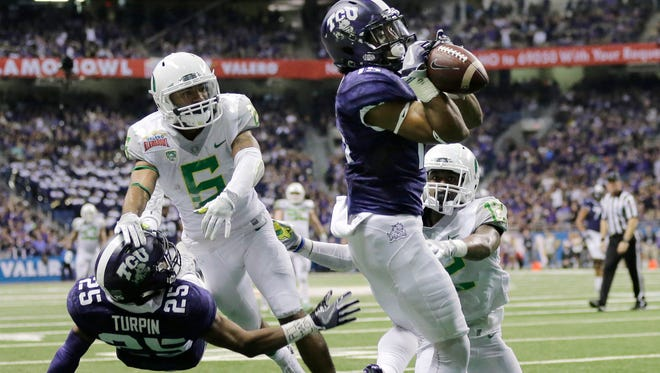 TCU wide receiver Jaelan Austin (15) catches a touchdown pass in front of Oregon cornerback Chris Seisay (12) during the second half of the Alamo Bowl NCAA college football game, Saturday, Jan. 2, 2016, in San Antonio.