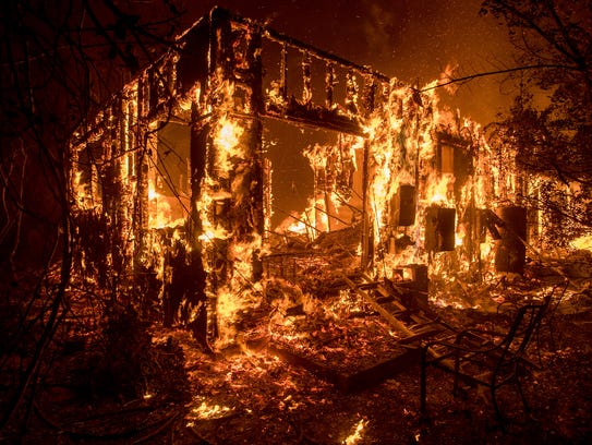 Flames consume a home as a wildfire burns in Ojai, Calif., on Dec. 7, 2017.
