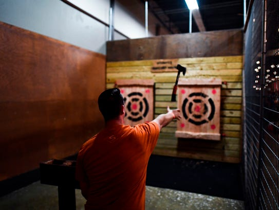 A man throws a hatchet as he plays hatchet throwing
