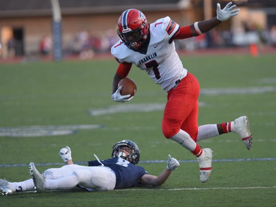 Eluding a tackle Friday night is Livonia Franklin running