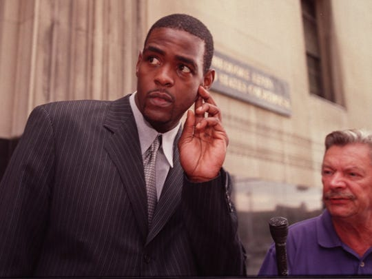 Chris Webber, left, tugs at his ear as he ponders a question from radio reporter Rod Hansen, right, of WJR, after he testified to a grand jury in regard to the investigation of University of Michigan booster Ed Martin at the U.S. Federal Courthouse in Detroit, Wednesday, August 2, 2000.Webber was accompanied to court by his father Mayce Webber.