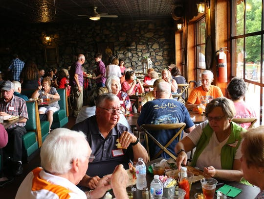 Customers eat at tables overlooking the Tennessee River
