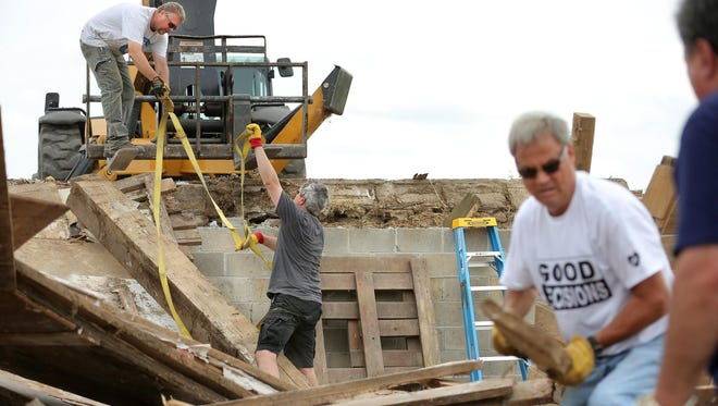 Mark Frisbie (left), an employee of Shepherd Community Center, and Jay Chapman, of Indianapolis, tie up a giant beam Sunday, Aug. 23, 2015, as a crew dismantles an old barn in Noblesville. The barn was donated by Mark Gradison of Gradison Design-Build. Proceeds from the reclaimed wood will benefit the community center on Indianapolis' Eastside.