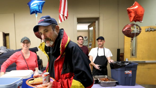 Bob Jones, 71, of Salem, gets a plate with a hot dog, cookies and a soda during a Super Bowl party at the Union Gospel Mission men's shelter in downtown Salem on Sunday, Feb. 7, 2016.