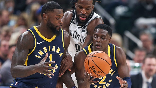 Indiana Pacers guard Lance Stephenson (1) takes a pass off from Indiana Pacers guard Darren Collison (2) as Brooklyn Nets forward DeMarre Carroll (9) tries to interfere during second quarter action between the Indiana Pacers and Brooklyn Nets at Banker's Life Fieldhouse, Indianapolis, Saturday, Dec. 23, 2017.