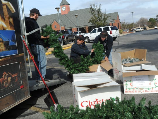 Matt Pannell, from left, Michael Conant,  and Jaime Hernandez from Christmas Decor remove holiday decorations from an Abilene Country Club building Tuesday, Jan. 3, 2017.