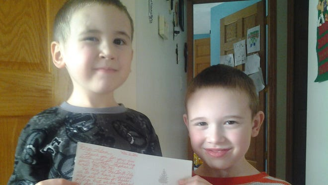 Stephen Smith, 4, displays the letter from Santa with brother Adam Smith, 7, in their Lowell home on Friday.