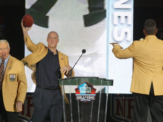 """Jim Kelly throws a pass to Andre Reed after Reed's Hall of Fame speech on Saturday. The pass put a cap on an emotional evening in Canton, Ohio. Reed called Kelly, """"the toughest individual I've ever met in my life,"""" in his speech."""