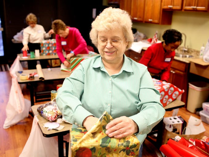 Helen Hollingsworth wraps presents while volunteering  as part of the Be a Santa to a Senior program sponsored by Home Instead Senior Care. December 9, 2013