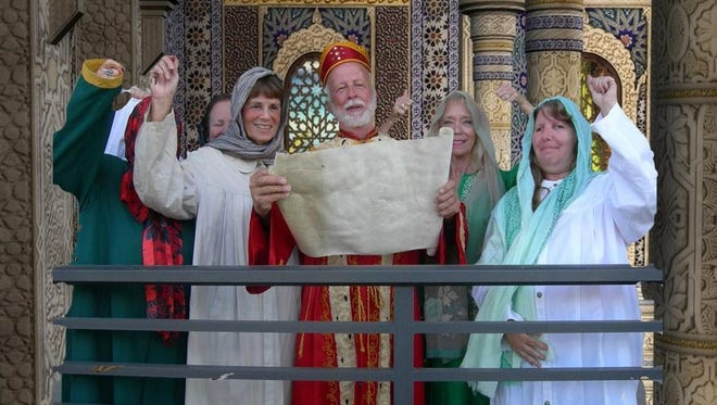 Mordecai played by Tom Miess in the center reads from the Scroll of Esther at the Community Free Synagogue Purim celebration.