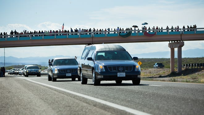 A hearse carrying the body of Hatch Police Officer Jose Chavez, who was killed in the line of duty Friday, makes its way south, under the Interstate 25 overpass that leads into Hatch, Monday, August 15, 2016.