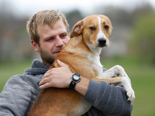 Corey Wright and his dog Tank, a beagle-lab mix dog, on Monday, March 27, 2017. Wright who is currently homeless and living in his car often takes his dog hiking in Busiek State Forest. On a recent trip there he found a dog who had been abandoned and left with a note, a dog bed and food.