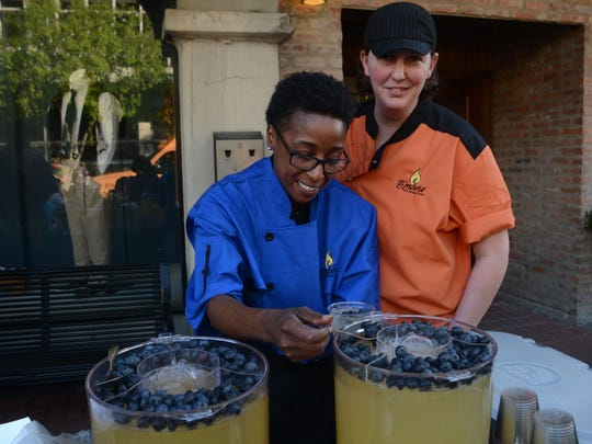 Embers general manager Bridget Gilchrist (right) watches as Ebony Phillips, Embers kitchen manager tops a peach sangria off with blueberries. Embers was among the restaurants participating in Dinner on the Bricks Thursday in downtown Alexandria.