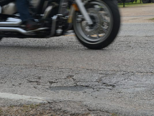 ANI Vandenburg Drive Vandenburg Drive between Highway 28 West and the England Airpark entrance is cracked with patched potholes.-Melinda Martinez/The Town Talk