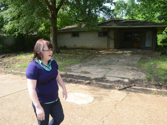 Carrie Robinette, grant administrator for the Rapides Area Planning Commission, talks about the Greenway Park Subdivision Acquisition Project as she walks past one of the houses on Linwood Lane that will be demolished as part of the plan.