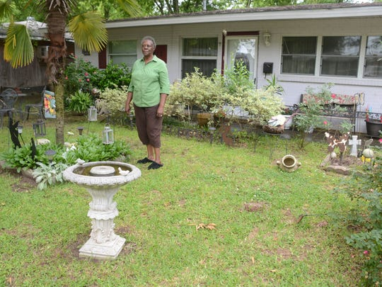 "Alice Jackson stands in her front yard on Linwood Lane after talking about how she and her husband will move from their home of 35 years so it can be demolished for a flood-mitigation project. ""I'm kind of looking forward to it (moving) for a change of pace,"" she said."