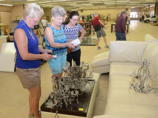 Melba Peart, Claudia Hathorn and Fern Albin look at a couch and other Rapides Parish Coliseum items up for auction. Peart was looking to bid on concession stand items while Hawthorn was looking to bid on chairs for her church.