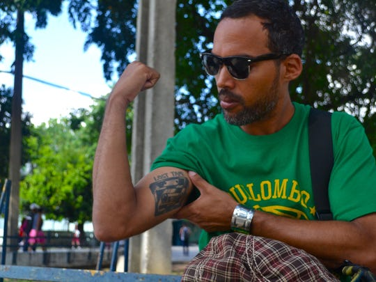 Alexei Jacomino shows off his tattoos in a park in Havana.