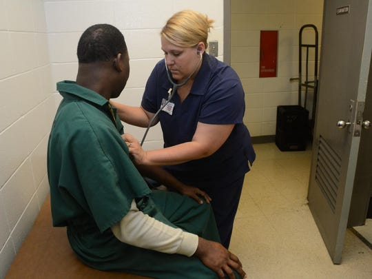Stacey Causey (right), a family nurse practitioner with Nortec, checks a prisoner in the medical examination room of Detention Center I in the Rapides Parish Courthouse annex. Nortec has been contracted by the Rapides Parish Sheriff's Office to provide medical care for inmates.