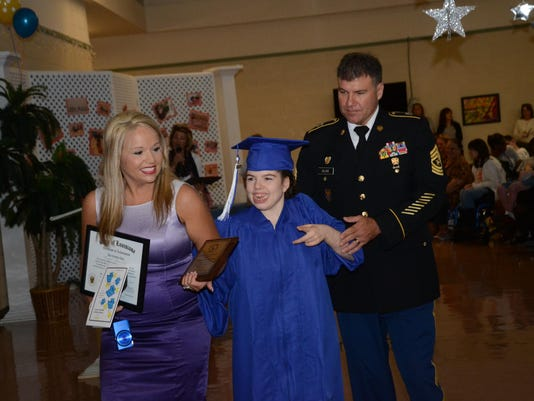 ANI La. Special Education graduation Holly Delrie (left) and husband Sgt. Maj. Darren Delrie walk with daughter Moran Alexis Delrie after Morgan was awarded a certificate of achievement from the Louisiana Special Education Center. Morgan was also presente