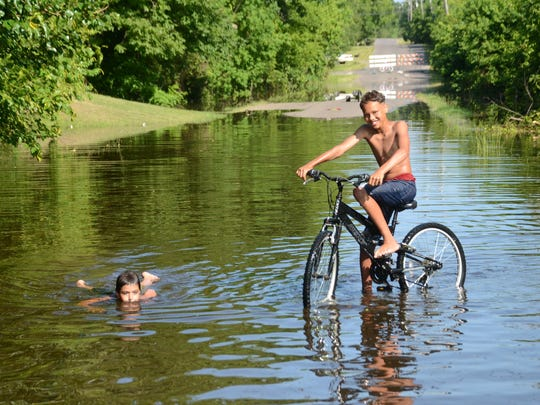 Jordan LaCaze (left), 12, lies in floodwater covering Crepe Myrtle Street in the Wardville of Pineville as Kameron Means, 12, rides a bike through the water on Friday. The boys, along with Kameron's brother Kody Means, 11, have been swimming in floodwater alongside the street, of which a section is blocked off because of flooding.