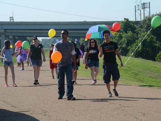 Timothy Zannotti (left) and Ariel Espinoza, both soldiers stationed at Fort Polk, walk with others Saturday in the Cenla Pride Stroll at the Levee Park Amphitheatre in downtown Alexandria..