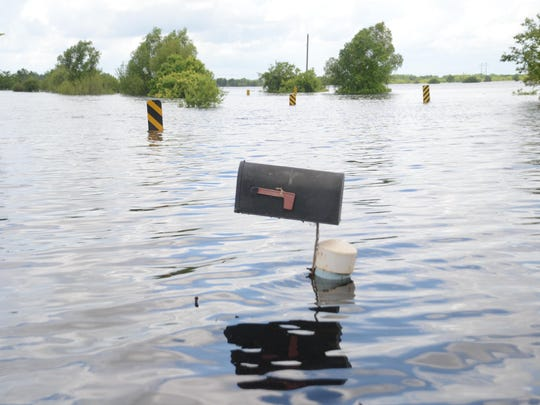 A mailbox and road markers line the area where Rigolette Road is located beneath the water.