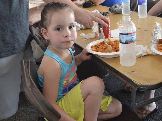 Rylie Yale, 5, from the Town of Maine, enjoys some pasta at the final day of last year's St. Anthony Feast Days.