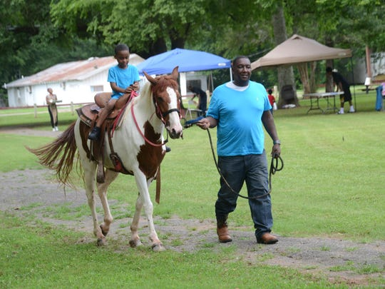 Billy Jacobs gives Jamari Woodfox a ride on one of his two horses at the Children's Fun in the Park at Frank O. Hunter Park which was part of the Juneteenth celebration held Saturday. Jacobs and Jimmy Walden brought their horses for children to ride.