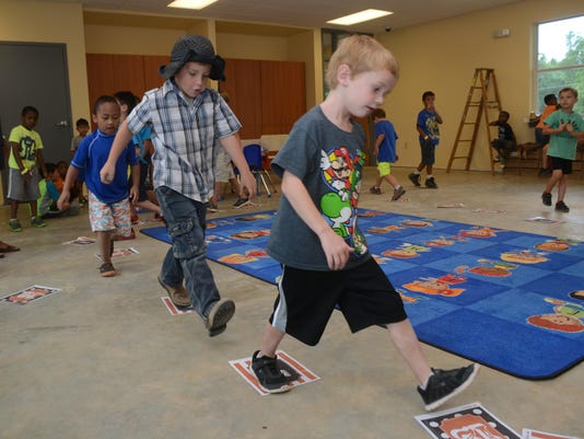 ANI YWCA Camp Austin Purvis (front, right) and Jorden Lane do a cake walk during the Country Western Carnival held Friday, June 19, 2015 at the YWCA on St. James Street in Alexandria.-Melinda Martinez/The Town Talk