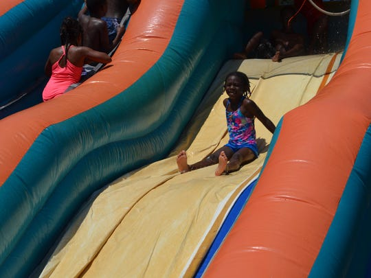 Jakayiah Coleman, 6, slides down the Big Kahuna inflatable water slide at the Rec2U event in Alexandria City Park.