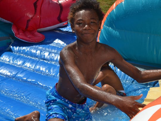 Tray Dontrell, 11, enjoys the Big Kahuna water slide at the Rec2U event Friday.