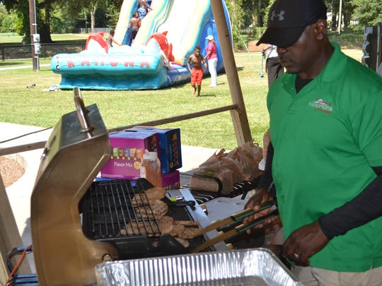 Ralph Perry of the Alexandria Parks and Recreation Department cooks hamburgers at the Rec2U event in Alexandria City Park.