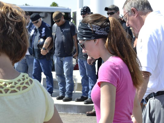 Taylor Doty, front middle, holds her mother Linda Doty's hand, left, and Madison County Sheriff's Office Public Information Officer Tom Mapes' hand, right, as Mapes prays before the poker run to benefit Taylor Doty on Saturday.