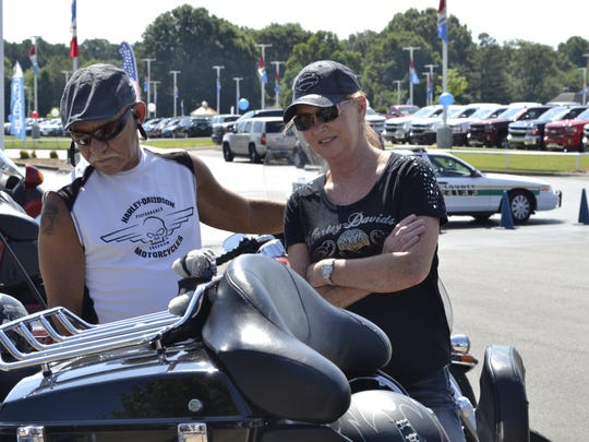 Rider Mike Johnson from Crime Stoppers, left, and Marilyn Hickman, right, admire a friend's motorcycle before the poker run Saturday at Serra of Jackson.