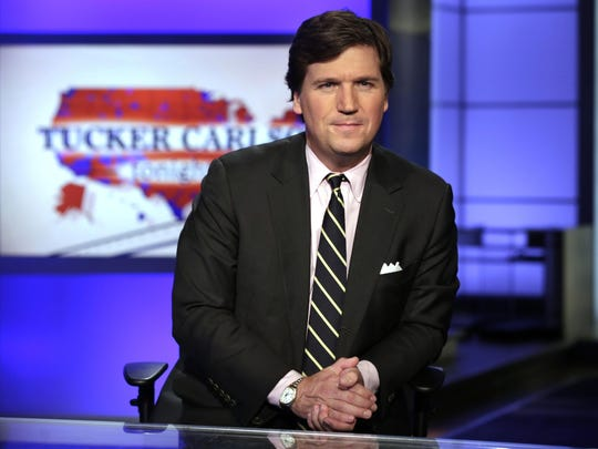 """In this March 2, 2017 file photo, Tucker Carlson, host of """"Tucker Carlson Tonight,"""" poses in a Fox News Channel studio, in New York. The liberal advocacy group Media Matters for America this week released two batches of recordings Carlson made as a guest on a radio show where he made denigrating remarks about race and gender. It was timed to coincide with Fox's first-ever sales meeting with advertisers on Wednesday, March 12, 2019. Media Matters says it wants to pressure Fox into better behavior by making advertisers aware of what is being said on the air. Carlson says critics want to shut Fox down."""