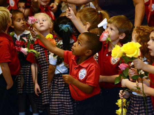 St. Frances Cabrini Pre-K student Aiden Gordon, 3, hands a rose to the priest during the school's celebration of the feast day of St. Therese on Wednesday.