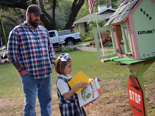 John Welch and his daughter Jinks, 6, look at some of the books left in their Little Free Library in front of their home on Marye Street in Alexandria on Wednesday, October, 29, 2014. --Tia Owens-Powers/ towens@thetowntalk.com